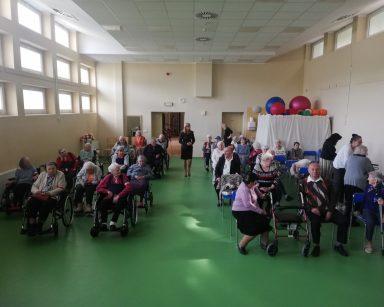 Seniorzy i pracownicy zbierają się na sali. Część z nich już siedzi.