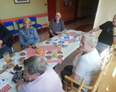 Przy stole seniorzy, kierowniczka Ilona Gajewska. Wszyscy się śmieją. Na stole soki, czekolada, kartki z różnymi symbolami.