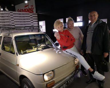 Muzeum Emigracji w Gdyni. Roześmiana trójka seniorów pozuje do zdjęcia przy samochodzie marki 126 p, czyli maluchu.