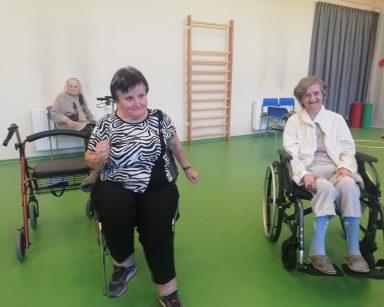 Dwie seniorki w trakcie ćwiczeń na siedząco. Przy ścianie seniorka na krześle. Dalej drabinki.