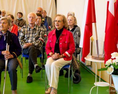 Seniorzy siedzą na sali. Przy ścianie wazon z białymi i czerwonymi różami, flagi polski na stojaku.