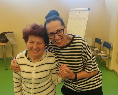 Terapeutka Magdalena Poraj-Górska obejmuje seniorkę. Uśmiechają się szeroko.