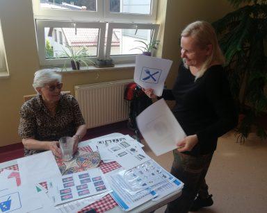 Neurologopedka Anna Szmaja-Wysocka i seniorka. Obie się śmieją. Na blacie kolorowe serwetki, kartki z symbolami.