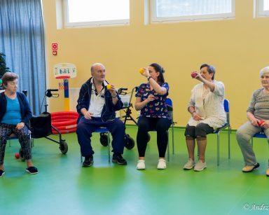 Fizjoterapeutka Martyna Józefczyk prowadzi ćwiczenia. Siedzi z czworgiem seniorów, ćwiczą z piłeczkami.