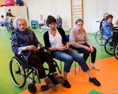 Terapeutka Ania Rzepczyńska siedzi między seniorkami. W dalszej części sali gimnastycznej seniorzy uczestniczą w zajęciach.