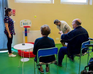 Sala gimnastyczna. Fizjoterapeutka Martyna Józefczyk stoi przy koszu do gry w mini koszykówkę. Przed koszem troje seniorów.