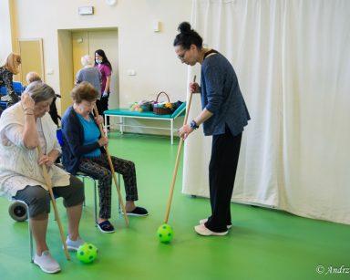 Terapeutka Magdalena Poraj-Górska, dwie seniorki ćwiczą z drewnianymi drążkami i dwiema piłkami. Dalej pracownicy i seniorzy.