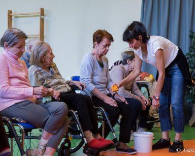 Na sali gimnastycznej siedzą seniorzy. Terapeutka Ania Rzepczyńska pochyla się nad seniorką.