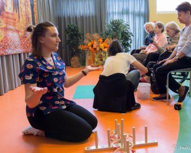Na sali gimnastycznej siedzą seniorzy. Fizjoterapeutka Martyna Józefczyk klęczy przy ringo i rozkłada ręce.