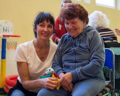 Na sali gimnastycznej obok siebie uśmiechnięta seniorka i terapeutka Ania Rzepczyńska. Z tyłu inni seniorzy i pracownicy.