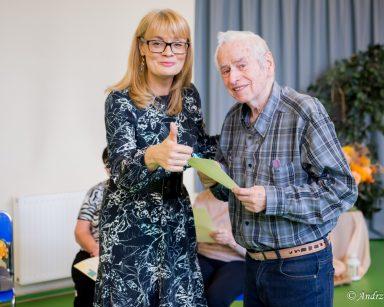 Sala gimnastyczna. Uśmiechnięta dyrektorka Agnieszka Cysewska unosi kciuk w górę i obejmuje seniora. Senior uśmiecha się.