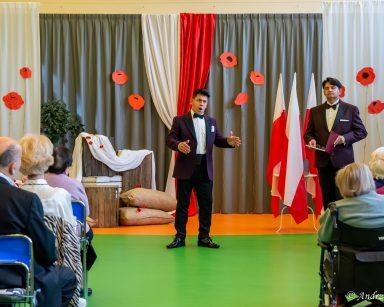 Artyści Jacek Szymański i Dariusz Wójcik przed seniorami. Za nimi biało-czerwone dekoracje, czerwone maki, polskie flagi.