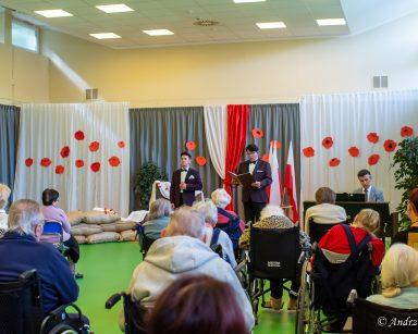 Artyści w trakcie występu przed seniorami. Za nimi dekoracja z czerwonych maków, polskie flagi.