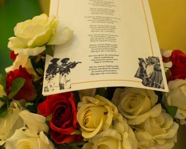 Na bukiecie z białych i czerwonych róż kartka. Na kartce tekst hymnu Polski, na dole strony ludzie w strojach ludowych.