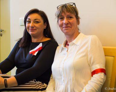 Kierowniczka Ewa Siłakiewicz-Witt z biało-czerwoną opaską i terapeutka Małgorzata Jancelewicz z biało-czerwona wstążką.