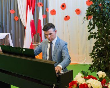 Paweł Zawada gra na fortepianie. Obok wazon z białymi i czerwonymi różami. W tle polskie flagi i papierowe, czerwonych maków.