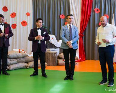 Sala udekorowana papierowymi czerwonymi makami. Na środku kierownik Arkadiusz Wanat i artyści.
