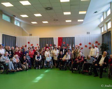 Artyści, seniorzy i pracownicy pozują do zdjęcia. Część ma przypięte biało-czerwone wstążki lub założone na ramię opaski.