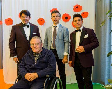 Artyści Jacek Szymański, Dariusz Wójcik i Paweł Zawada pozują do zdjęcia z seniorem.