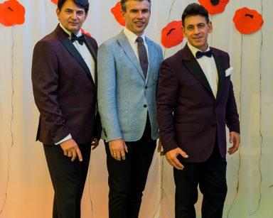 Jacek Szymański, Dariusz Wójcik i Paweł Zawada stoją uśmiechnięci. Za nimi dekoracja z czerwonych, papierowych maków.