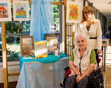 Dyrektorka Agnieszka Cysewska i seniorka. Obok na stole wystawione oprawione rysunki.