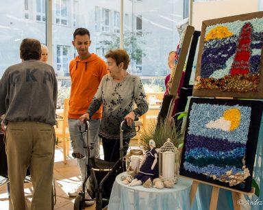 Na sztalugach obrazy o tematyce morskiej wykonane z tkanin. Seniorzy i pracownicy oglądają wystawę.