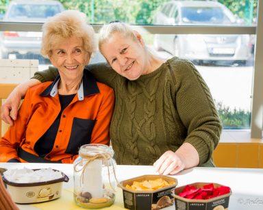 Seniorki siedzą przy stole. Uśmiechają się. Przed nimi materiały do prac plastycznych.