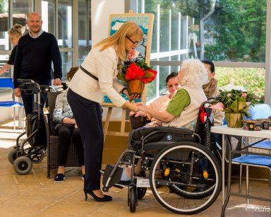 Wystawa w ogrodzie zimowym. Dyrektorka Agnieszka Cysewska wręcza kwiaty seniorce.