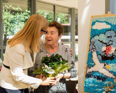 Dyrektorka Agnieszka Cysewska wręcza kwiaty seniorce. Obejmują się i uśmiechają. Obok obraz wykonany z tkaniny.