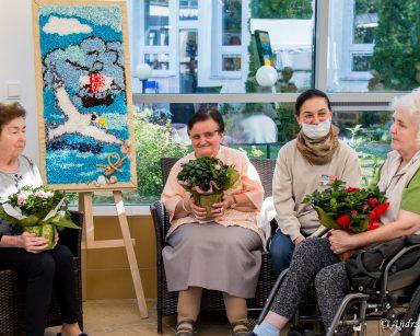 Wolontariuszka i trzy seniorki. Każda seniorka trzyma ozdobną doniczkę z kwiatami. Obok obraz wykonany z kolorowych tkanin.