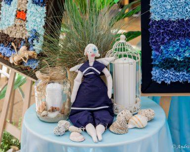 Na stole dekoracja: materiałowa lalka w granatowym, marynarskim ubranku, muszle, kamyki, lampion, świeca.