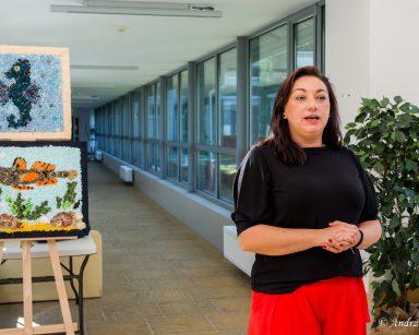 Terapeutka Małgorzata Jancelewicz prowadzi warsztaty. Na sztalugach obrazy z konikiem morskim i rybą wykonane z tkanin.