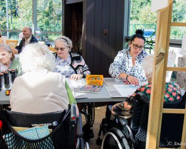 Terapeutka Magdalena Poraj-Górska i seniorzy przy stołach. Na blatach kartki, kolorowe kredki, pastele.