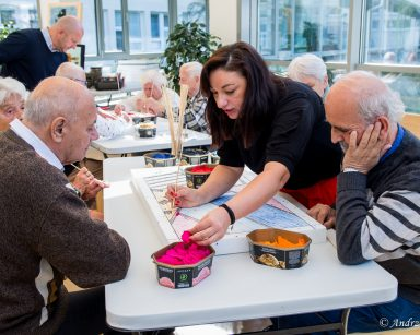 Terapeutka Małgorzata Jancelewicz pokazuje seniorom jak stworzyć obraz na styropianie, za pomocą skrawków kolorowych tkanin.