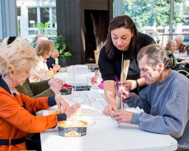 Terapeutka Małgorzata Jancelewicz pokazuje seniorom jak stworzyć obraz na styropianie za pomocą skrawków kolorowych tkanin.