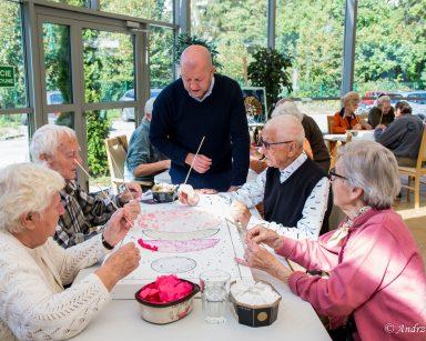 Przy stole seniorzy tworzą wspólnie obraz z kawałków tkanin. Obok kierownik Arkadiusz Wanat.