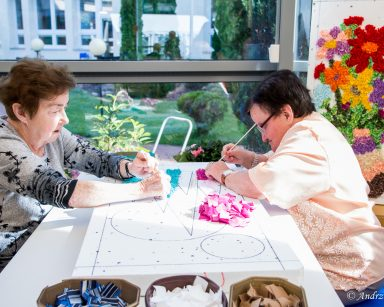 Przy stole dwie seniorki. Wspólnie pracują nad obrazem. Wbijają patyczkami kawałki kolorowych tkanin w styropian.