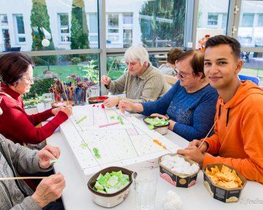 Przy stole seniorki i referent Krzysztof Hadjas. Wspólnie tworzą obraz z kawałków tkanin.