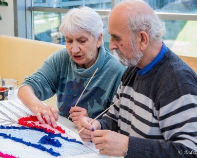 Przy stole seniorzy. Tworzą obraz wbijając patyczkami kawałki kolorowych tkanin w styropian.