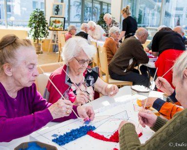 Ogród zimowy. Przy stolach pracownicy i seniorzy. Pracują nad obrazami. Patyczkami wbijają w styropian kawałki tkanin.