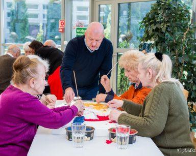 Przy stole seniorki tworzą wspólnie obraz z kawałków tkanin. Pomaga im kierownik Arkadiusz Wanat.