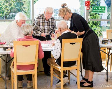Przy stole seniorzy i terapeutka Beata Brzozowska. Wspólnie pracują nad obrazem.