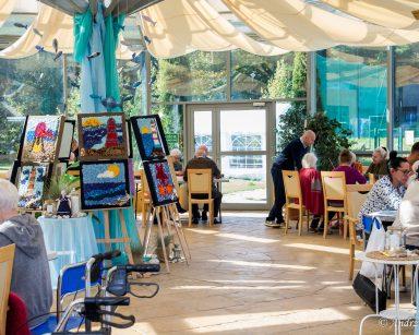Ogród zimowy. Na sztalugach obrazy o tematyce morskiej. Przy stolikach seniorzy, wolontariusze i pracownicy.