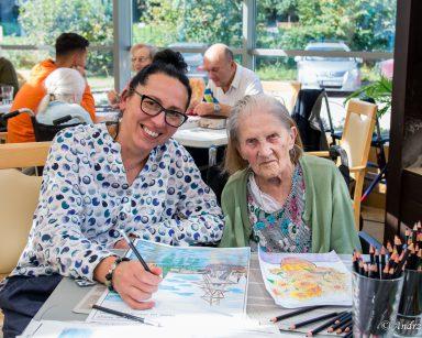 Warsztaty plastyczne. Terapeutka Magdalena Poraj-Górska i seniorka kolorują obrazy. W tle seniorzy i pracownicy przy stołach.