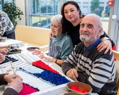 Terapeutka Małgorzata Jancelewicz obejmuje dwoje seniorów. Na stole częściowo wykonany obraz na styropianie.