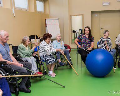 Seniorzy i fizjoterapeutka Paulina Winczura drewnianymi kijkami odpychają niebiską piłkę.