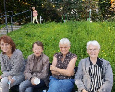 Cztery roześmiane seniorki siedzą na ławce na świeżym powietrzu. W tle spacerująca seniorka, zielona trawa i drzewa.