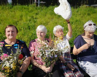 Cztery seniorki siedzą na ławce na świeżym powietrzu. Dwie z nich trzymają bukiety polnych kwiatów. Za nimi zielona trawa.
