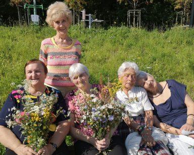 Pięć uśmiechniętych seniorek na świeżym powietrzu. Cztery siedzą na ławce, jedna stoi. Dwie trzymają bukiety polnych kwiatów.