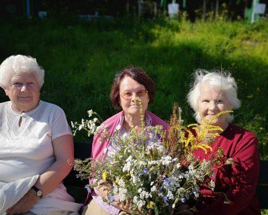 Trzy uśmiechnięte seniorki na ławce na świeżym powietrzu. Dwie z nich wspólnie trzymają bukiet polnych kwiatów.